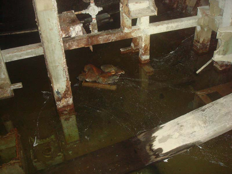 Dirty water, debris and rusty steel framework in the fuel storage area.